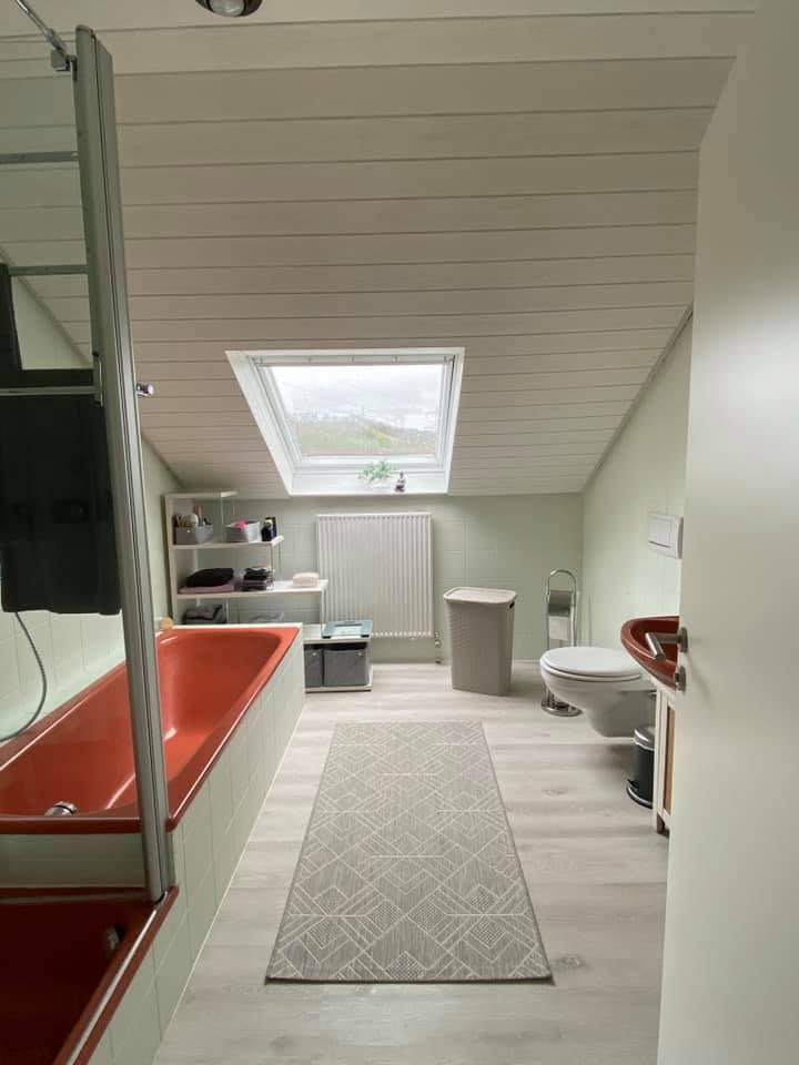 Zusammen mit der weißen Decke und den zart grün gestrichenen Fliesen wird die rote Badewanne zum Hingucker!